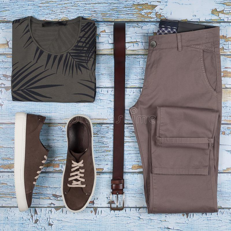 Tillfälliga dräkter för man` s Manskor, kläder och tillbehör på träbakgrund - t-skjorta, jeans, gymnastiksko, bälte Top beskådar  arkivbilder