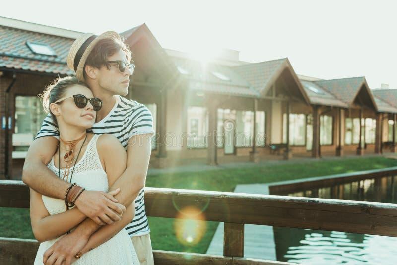 Tillfälliga par som omfamnar, medan stå på bron nära stugabyggnader arkivbilder
