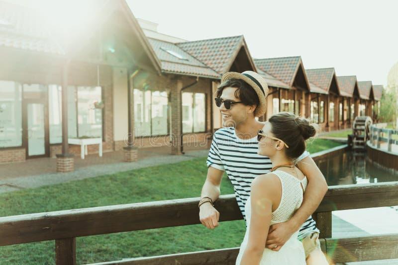 Tillfälliga par som omfamnar och ser bort, medan stå på bron arkivfoto