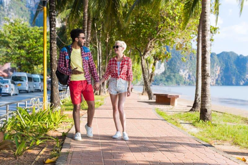 Tillfälliga parhållhänder som går i tropiska palmträd, parkerar, härliga ungdomarpå sommarsemester royaltyfri fotografi
