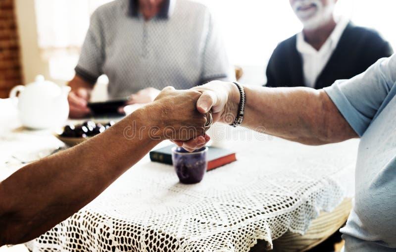 Tillfälliga pensionärer som skakar att hälsa för händer royaltyfri bild