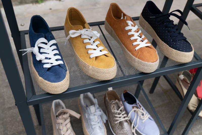 Tillfälliga skor på hyllor i gata shoppar royaltyfria bilder