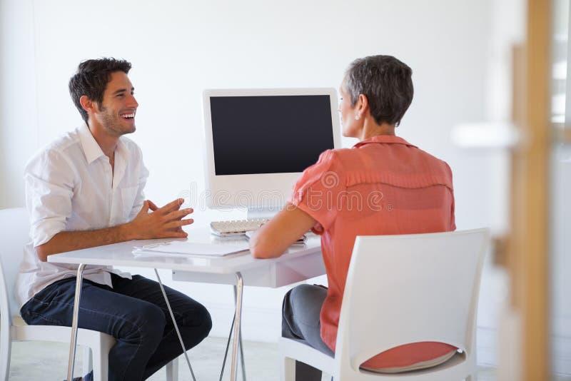 Tillfälligt affärsfolk som talar på skrivbordet och att le arkivfoton