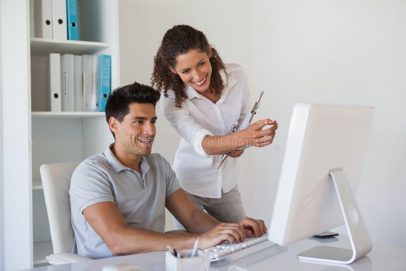 Tillfälligt affärslag som tillsammans ser datoren på skrivbordet royaltyfri fotografi