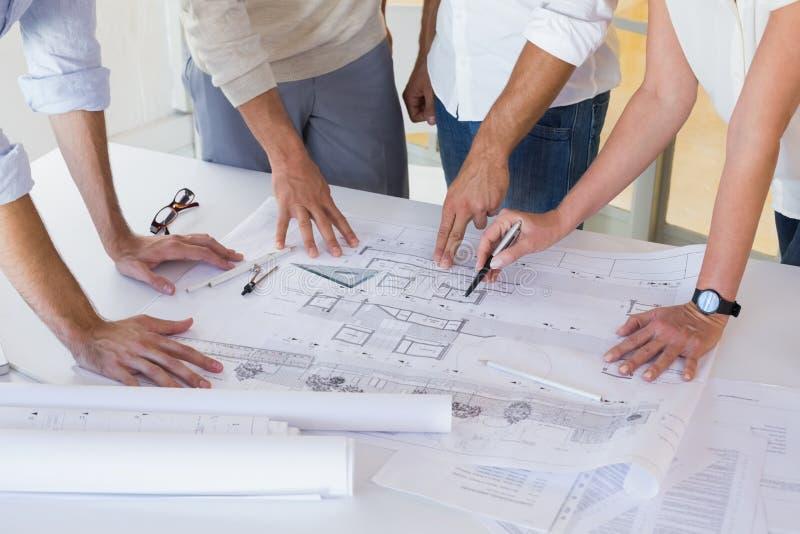 Tillfälligt arkitekturlag som tillsammans arbetar på skrivbordet fotografering för bildbyråer