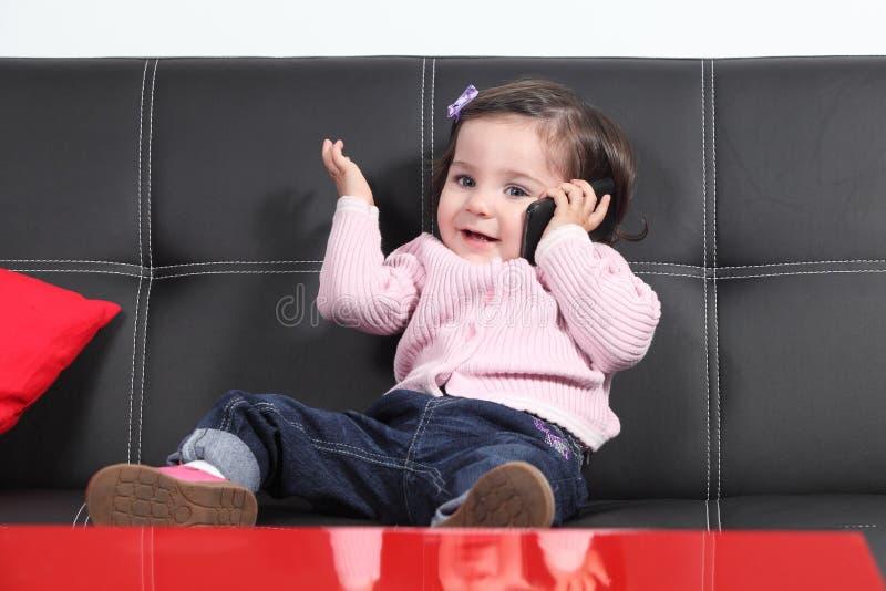 Tillfälligt behandla som ett barn att spela som är lyckligt med en mobiltelefon royaltyfria bilder