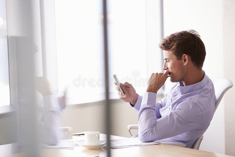 Tillfälligt klädd affärsman Using Mobile Phone i regeringsställning arkivfoton