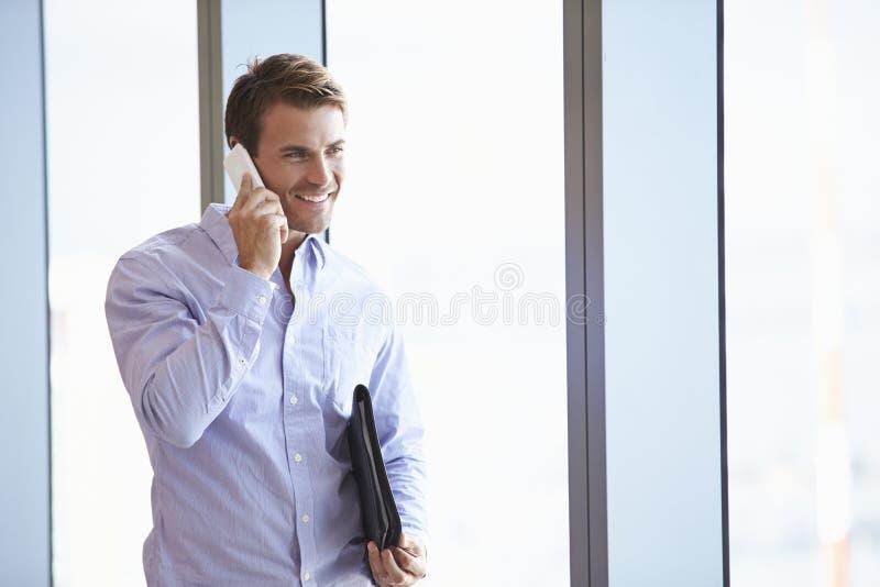 Tillfälligt klädd affärsman Using Mobile Phone i regeringsställning royaltyfri bild