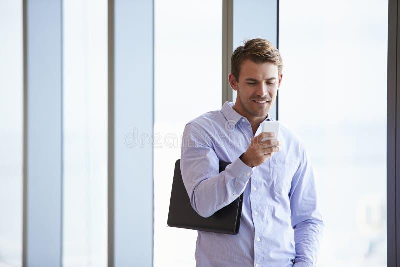 Tillfälligt klädd affärsman Using Mobile Phone i regeringsställning arkivbild