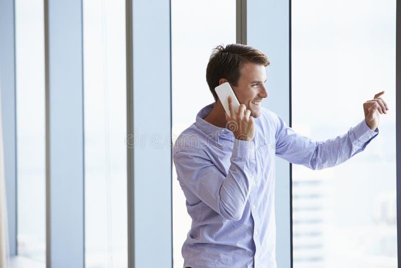 Tillfälligt klädd affärsman Using Mobile Phone i regeringsställning arkivfoto