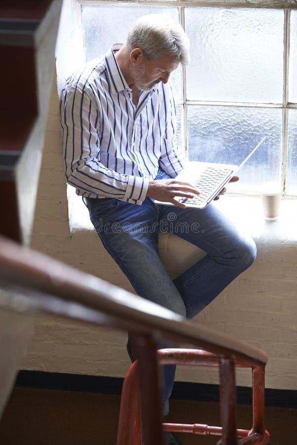 Tillfälligt klädd affärsman Working On Stairs i regeringsställning royaltyfri bild
