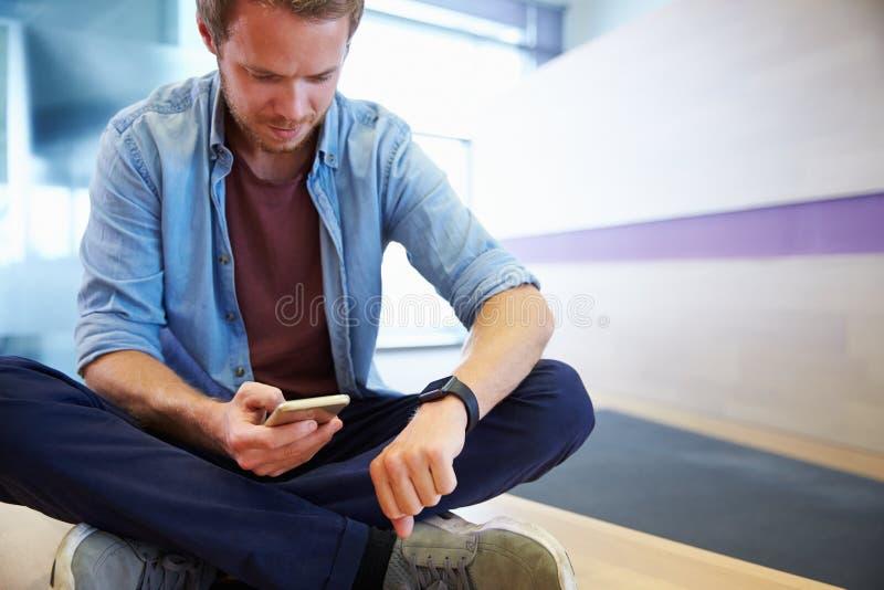 Tillfälligt klädd man med den smarta telefonen som ser hans klocka royaltyfri bild