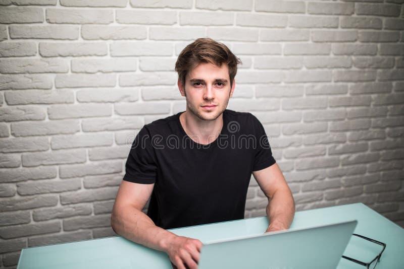 Tillfälligt klädd ung affärsman som använder en bärbar dator, medan sitta arkivbild