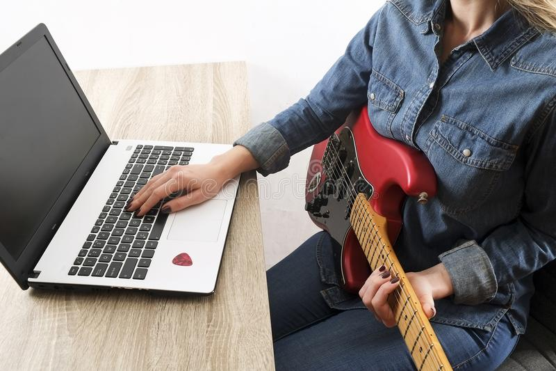 Tillfälligt klädd ung kvinna med gitarren som hemma spelar sånger i rummet bärbar datortabell Online-gitarrkursbegrepp ManG royaltyfri fotografi