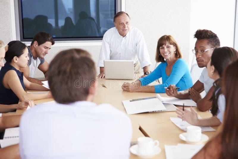Tillfälligt klädda Businesspeople som har möte i styrelse arkivbild
