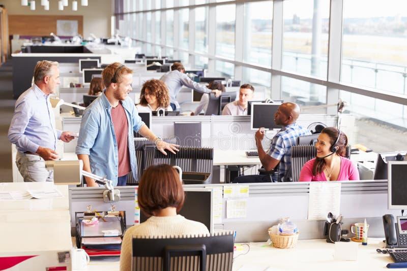 Tillfälligt klädda kollegor som talar i ett öppet plankontor arkivbilder