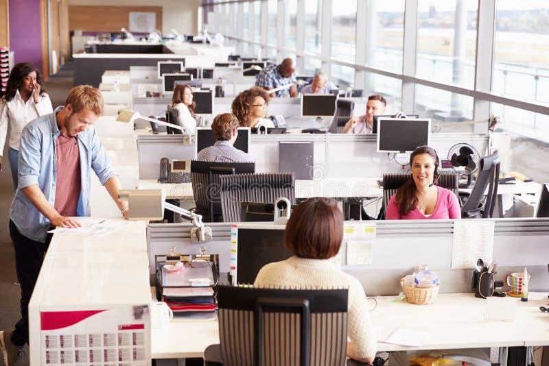 Tillfälligt klädda kollegor som talar i ett öppet plankontor royaltyfri fotografi