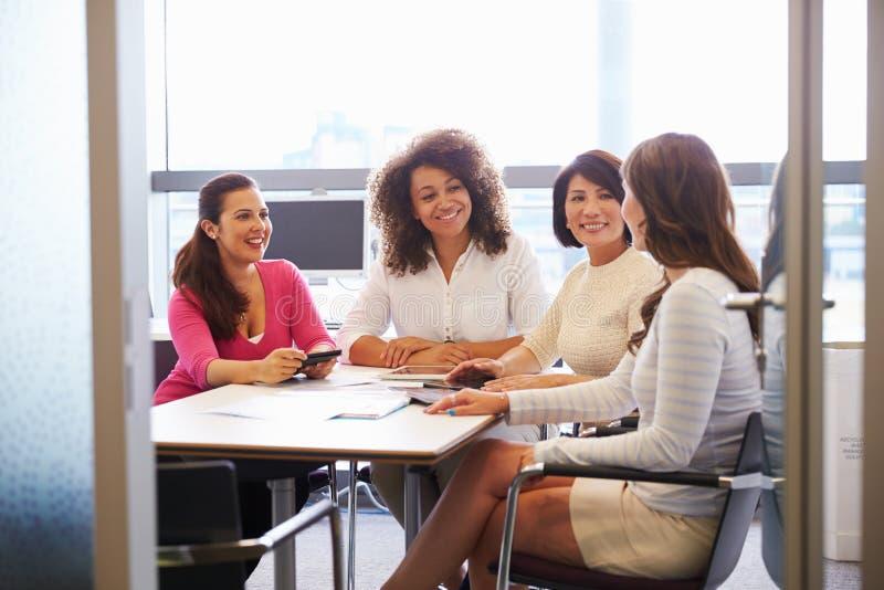 Tillfälligt klädda kvinnliga kollegor som talar i en mötesrum royaltyfri fotografi