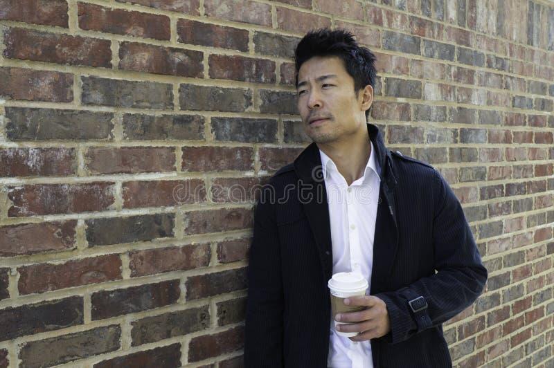 Tillfälligt klätt asiatiskt mananseende med kaffe arkivfoto