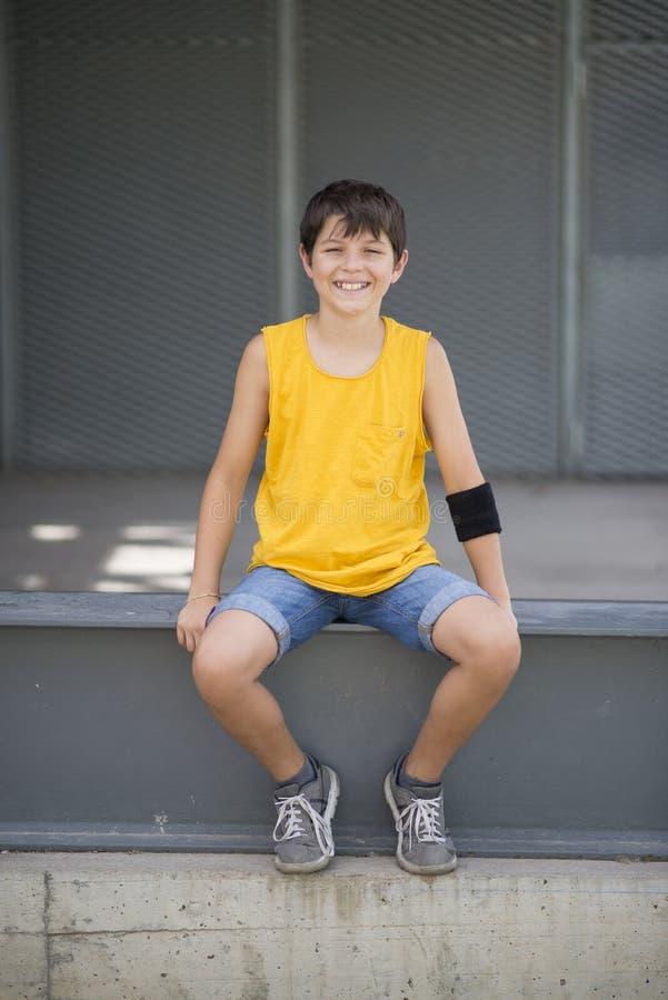 Tillfälligt klätt barn som utomhus ler den tonåriga ståenden för skateboradåkare arkivbild