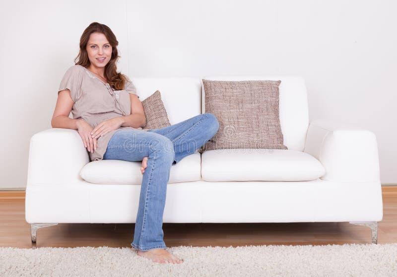 Tillfälligt kvinnasammanträde på en soffa arkivfoton