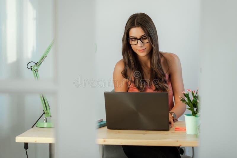 Tillfälligt kvinnasammanträde på skrivbordet som arbetar på bärbar datordatoren royaltyfria foton