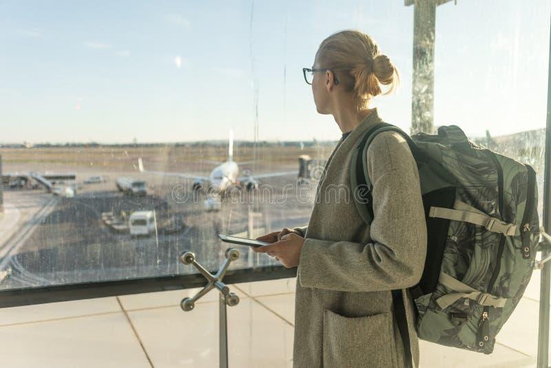 Tillfälligt kvinnlig handelsresande för påklädd på flygplatsen och att rymma den smarta telefonapparaten som ser till och med fly royaltyfri fotografi