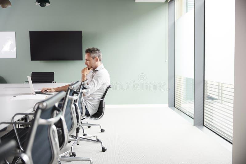 Tillfälligt mogen affärsman Working On Laptop för påklädd på styrelsetabellen i mötesrum royaltyfri bild