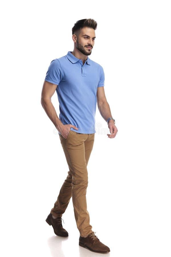 Tillfälligt påkläddmodell som bär ett ljust - blå polo som går och ser en sida arkivfoto