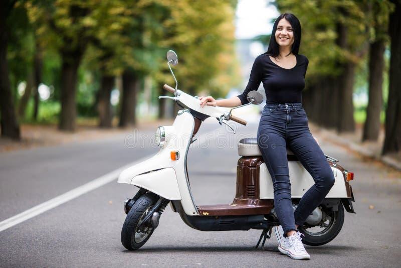 Tillfälligt sammanträde för ung kvinna på motosparkcykeln på den smala gatan i stad arkivfoton