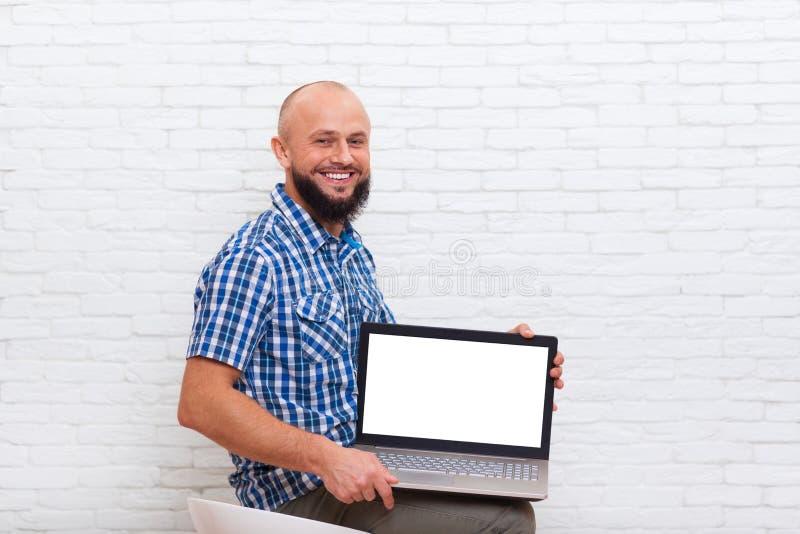 Tillfälligt skäggigt utrymme för kopia för skärm för dator för bärbar dator för håll för sammanträde för affärsman tomt fotografering för bildbyråer