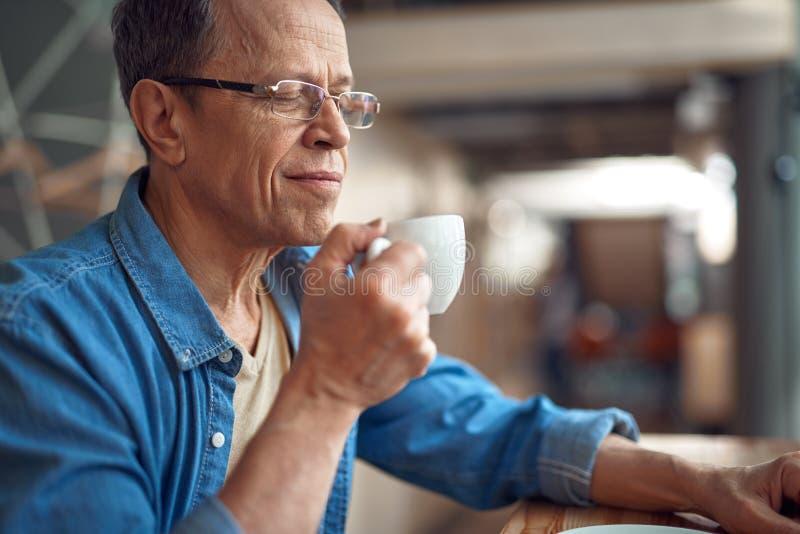 Tillf?llig stil ?ldrades mannen som sitter i kaf? med kaffe royaltyfri fotografi