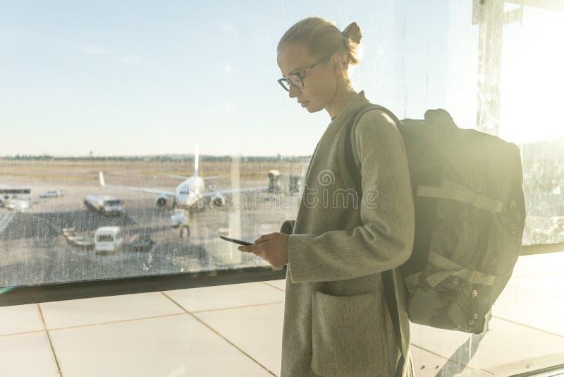 Tillf?lligt kl?dd kvinnlig handelsresande p? flygplatsen som framme ser den smarta telefonapparaten av att f?rbise f?r flygplatsp royaltyfri bild
