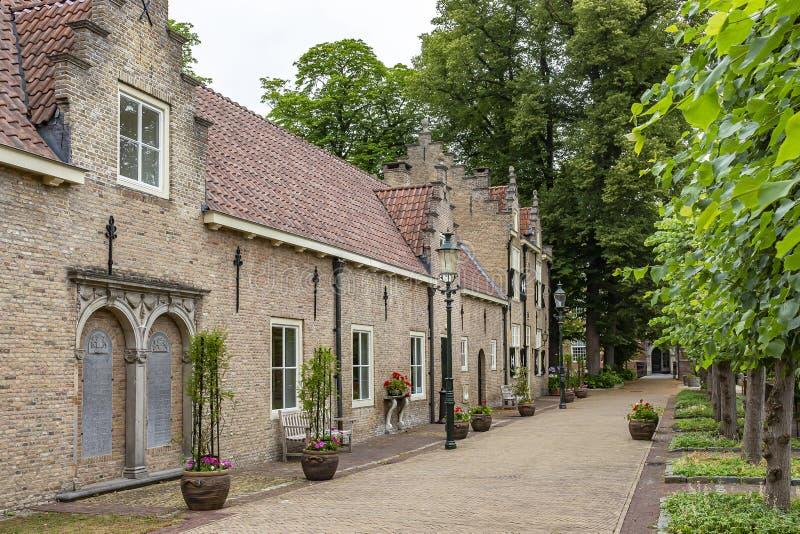 Tillfartsvägen med härliga stilfulla uthus och gamla träd av den Bouvigne slotten på Breda, Nederländerna royaltyfria foton