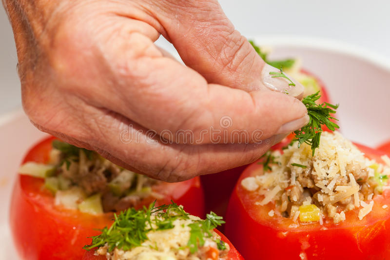 Tillfoga koriander till rå välfyllda tomater royaltyfri bild