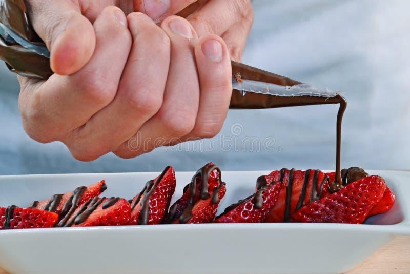 Tillfoga mörk chokladpralin på jordgubbar arkivbilder