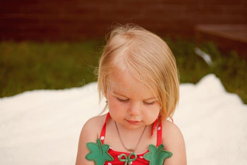 Tillfoga omsorg till ditt hår Frisyr för kläder för litet barn naturlig förtjusande blont barnhår Liten flicka med länge royaltyfri bild