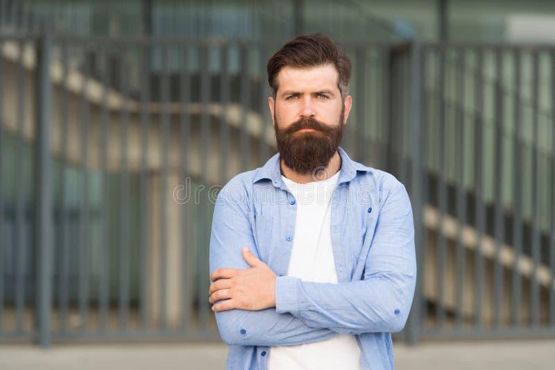 Tillfoga omsorg till hans mustasch Skägg och mustasch för allvarlig grabb bärande på stads- bakgrund Sk?ggig man med stilfullt arkivbild