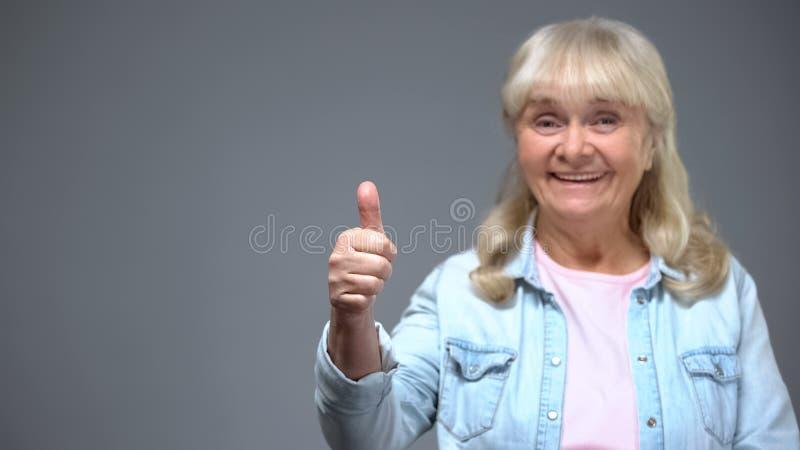 Tillfredsställd äldre kvinna som visar tumme-uppgesten, lycklig patient för medicinsk klinik arkivbilder