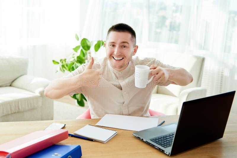 Tillfredsställd affärsman med arbete som i regeringsställning göras med koppen kaffe Lycklig ung man som arbetar på bärbara dator royaltyfri foto