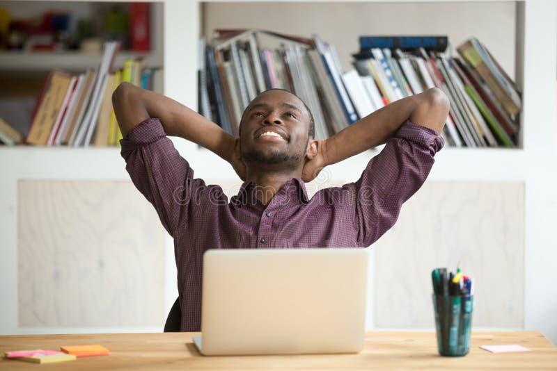 Tillfredsställd afrikansk amerikanbenägenhet i stol som är lycklig med arbete res royaltyfria bilder