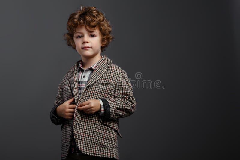 Tillfredsställd gullig pojke för pojke med iklätt rött lockigt hår en elegant dräkt, på en grå bakgrund, med kopieringsutrymme royaltyfri foto