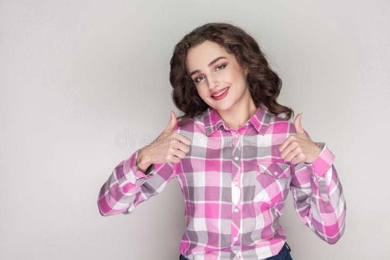 Tillfredsställd härlig flicka med den rosa rutiga skjortan, lockig hairst arkivfoton