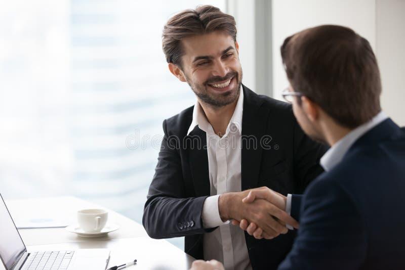 Tillfredsställd lycklig affärsman i dräkthandskakningaffärspartnern som gör avtal royaltyfri foto