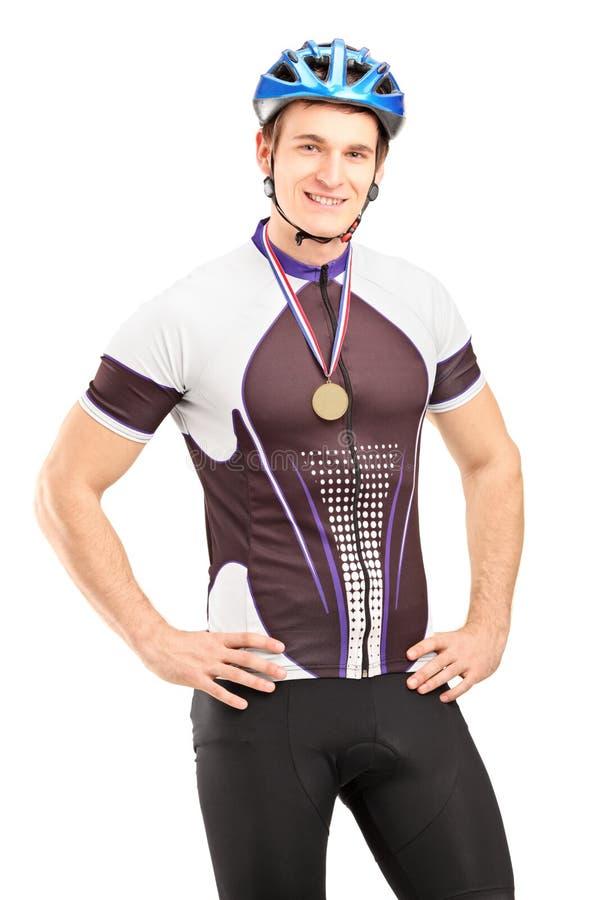 Tillfredsställd male cyklistvinnare som poserar med en guld- medalj royaltyfria bilder