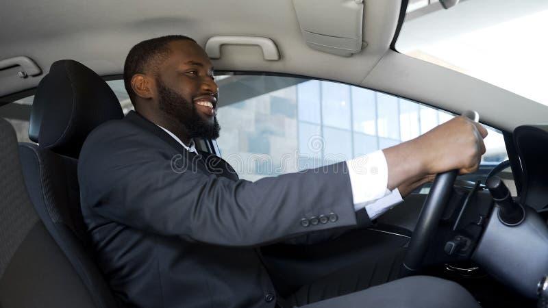 Tillfredsställd man i sammanträde för affärsdräkt i bilen, lyckat köp, lycka arkivbild