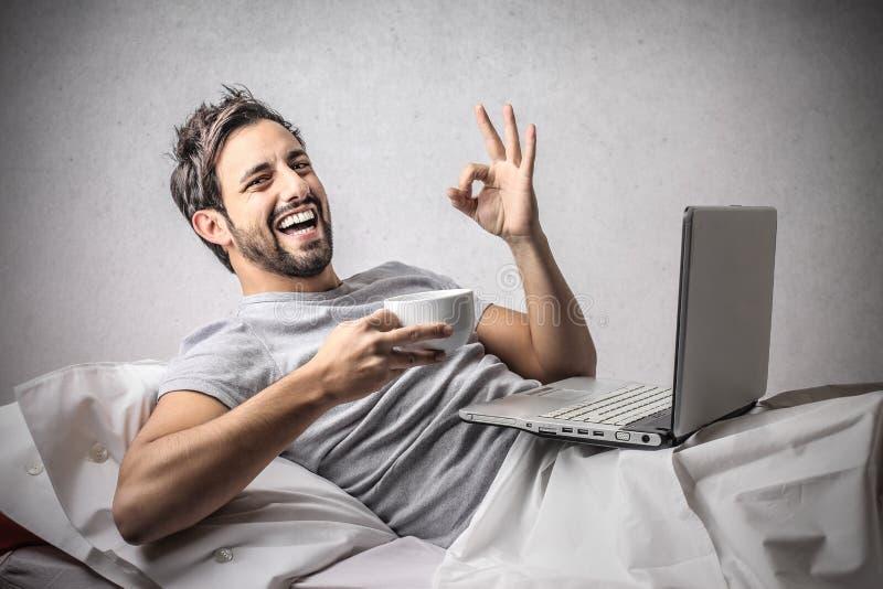 Tillfredsställd man som ler in i säng arkivbild