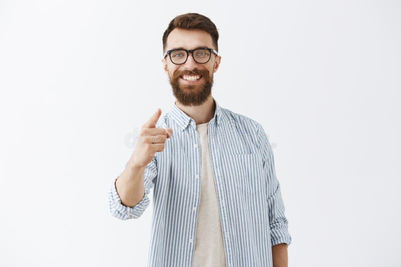 Tillfredsställd och behagen stilig manlig entreprenör som känner förtjust bra arbete av anställd peka med pekfingret royaltyfri fotografi