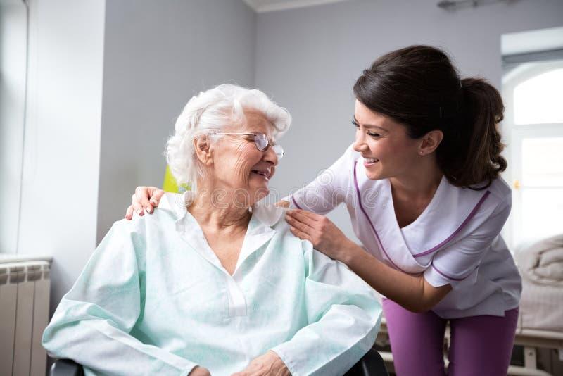 Tillfredsställd och lycklig hög kvinnapatient med sjuksköterskan arkivbilder