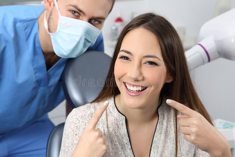 Tillfredsställd tålmodig visning för tandläkare hennes perfekta leende royaltyfria bilder